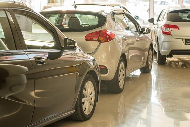 Neue autos im händlerausstellungsraum verwischten hintergrund