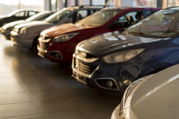 Neue autos im sonnenbeschienenen händlerausstellungsraum aus der nähe