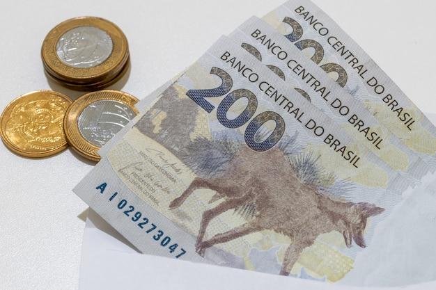 Neue banknoten und münzen aus brasilianischem geld mit dem bild des mähnenwolfs.