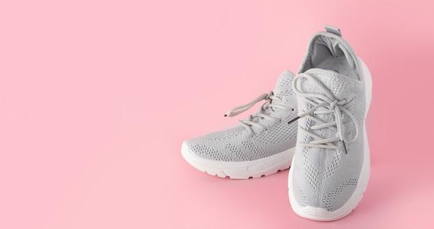 Neue bequeme turnschuhe, graue sportschuhe mit schnürsenkeln auf farbigem rosa hintergrund mit kopierraum. modische, stilvolle, schöne damenschuhe für frauen und jugendliche. minimalismus niemand