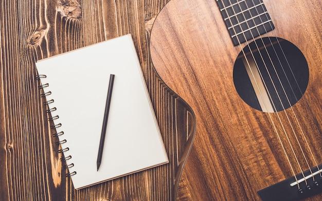 Neue braune gitarre auf holzbrett