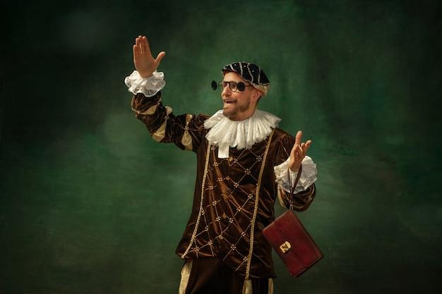 Neue brillen ausprobieren. porträt des jungen mannes des mittelalters in der weinlesekleidung mit holzrahmen auf dunklem hintergrund. männliches modell als herzog, prinz, königliche person. konzept des vergleichs von epochen, moderne, mode.