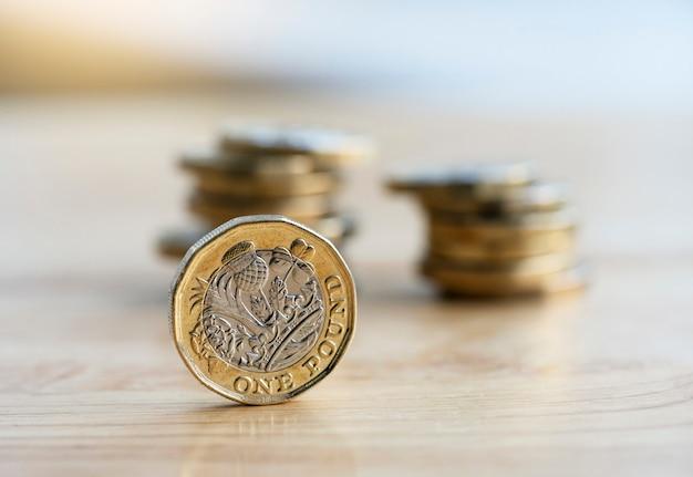 Neue britische pfundmünze mit undeutlichem reihenstapel prägt hintergrund