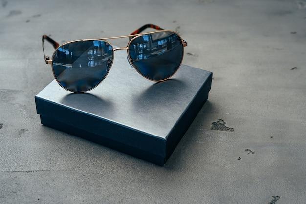 Neue dunkle fliegerbrille auf grauem betonhintergrund schließen