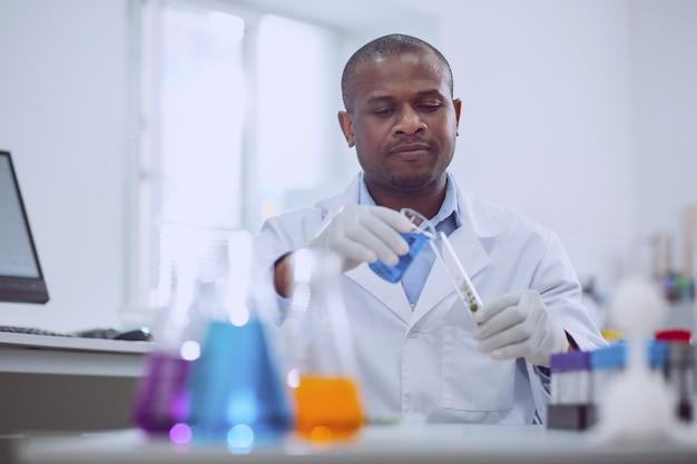 Neue ergebnisse. konzentrierter afroamerikanischer wissenschaftler, der während seiner arbeit im labor einen test durchführt