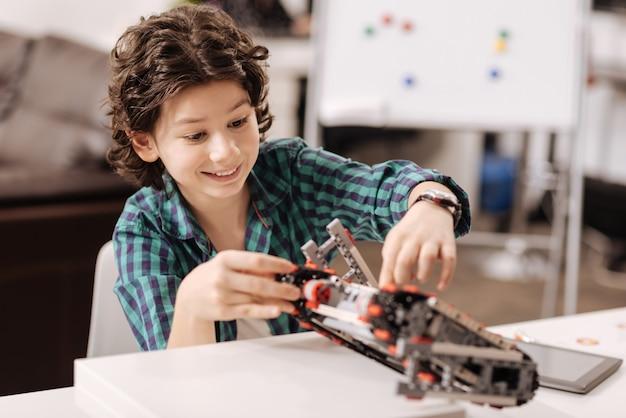 Neue fähigkeiten beherrschen. erfreuter freudiger erfinderischer junge, der im klassenzimmer sitzt und gerät berührt, während roboter programmiert