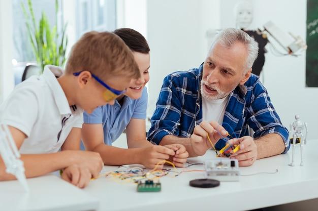Neue fähigkeiten. netter kluger mann, der seine enkelkinder ansieht, während er ihnen beibringt, wie man roboter baut