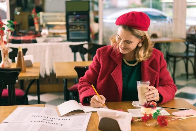 Neue gedichte. berühmter französischer schriftsteller, der einige neue gedichte schreibt, während er in der cafeteria sitzt und inspiration hat