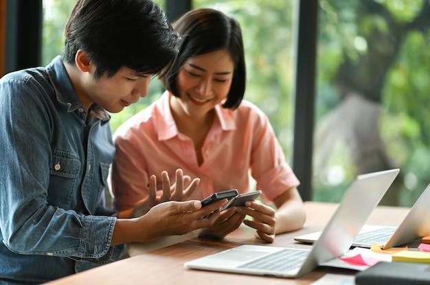Neue generation von jungen männern und frauen suchen mit dem smartphone nach informationen und einem laptop auf dem schreibtisch.