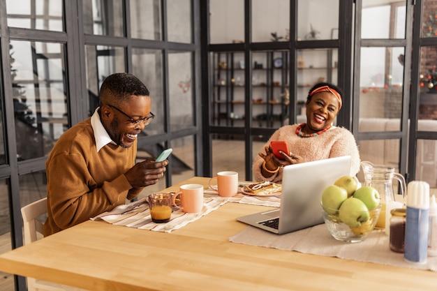 Neue geräte. freudiges nettes paar, das lächelt, während sie ihre modernen geräte benutzen