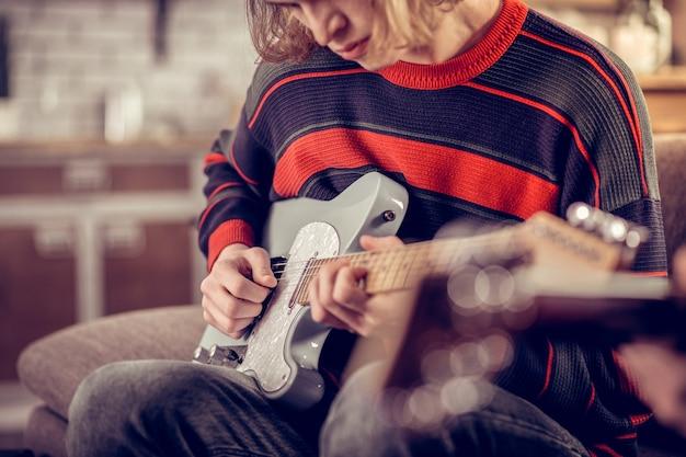 Neue gitarre. junger kreativer student, der seine neue gitarre hält und schöne melodie komponiert