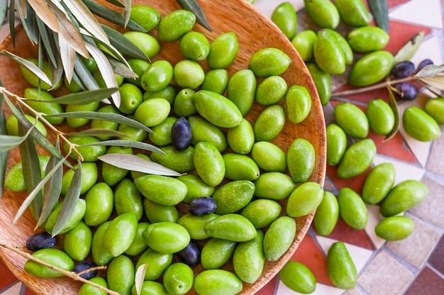 Neue grüne oliven mit niederlassungen und blättern. saisonale ernte in italien. ansicht von oben.