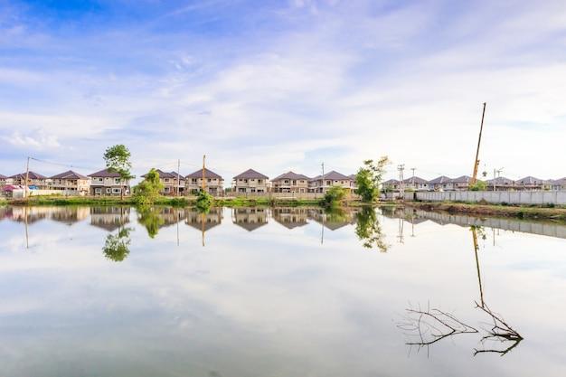 Neue hausbaureflexion mit wasser im see auf wohnbaustelle mit wolken und blauem himmel