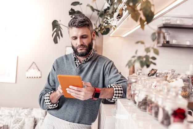Neue ideen. ernsthafter gutaussehender mann, der im internet surft, während er nach neuen ideen für sein café sucht