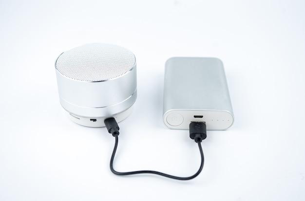 Neue kabellose graue no-name-mini-lautsprecher, die mit power bank auf weißem hintergrund aufgeladen werden