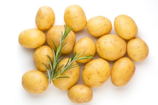 Neue kartoffel und rosemarin auf weißem hintergrund hautnah isoliert.