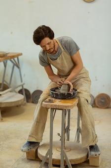 Neue kreation produzieren. dunkelhaariger mann mit bart, der mit professionellem rad neue tontöpfe herstellt