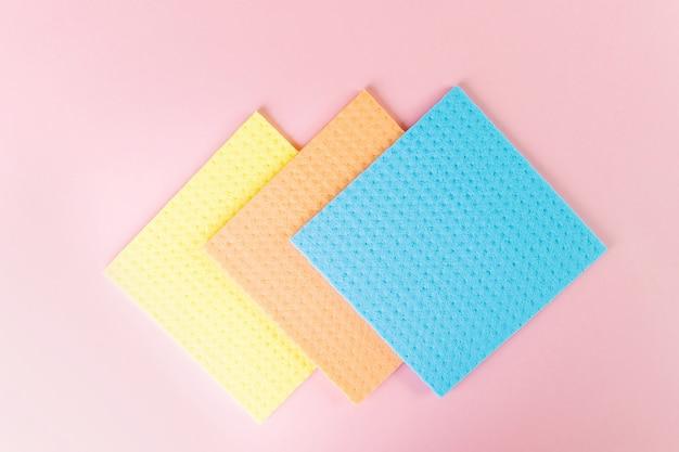 Neue lappen für die nassreinigung. blaue, gelbe und orangefarbene lappen auf rosa.