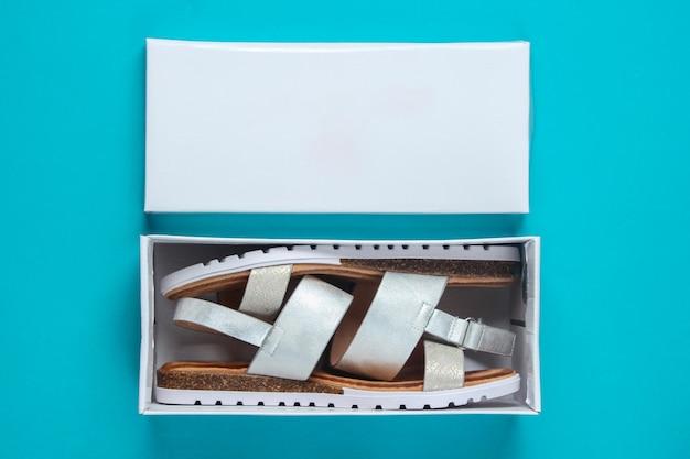 Neue ledersandalen für damen in einer box auf blau. draufsicht.