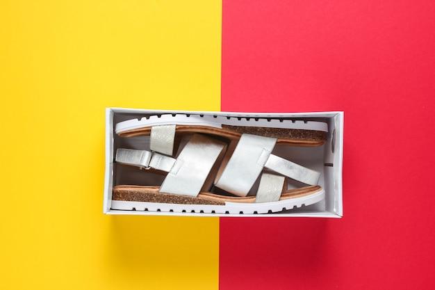 Neue ledersandalen für damen in einer box auf rot-gelb. draufsicht.