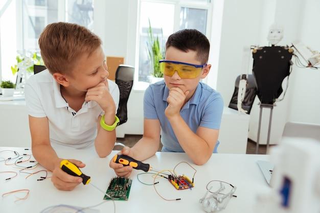 Neue lösungen. kluge, nette jungs, die nachdenken, während sie nach neuen ideen suchen