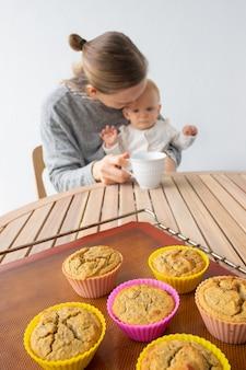 Neue mutter hält baby in den armen und trinkt tee
