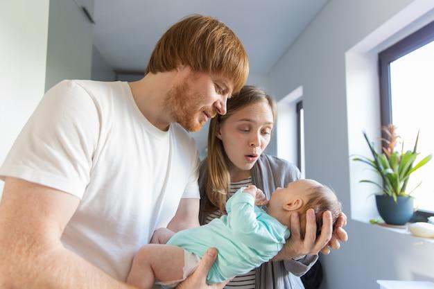 Neue mutter und vater, die mit baby sich verständigt