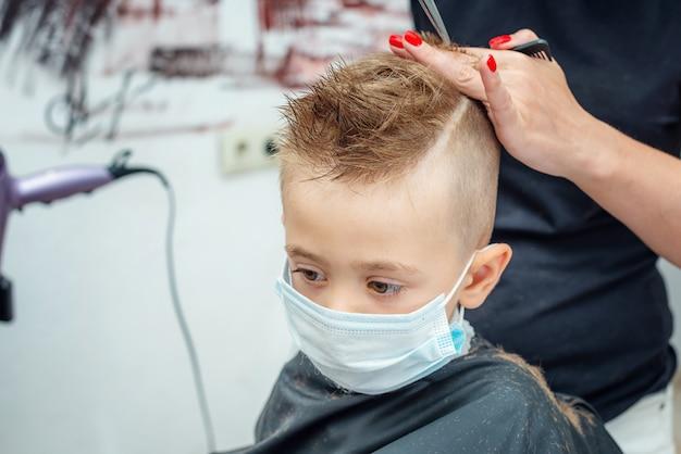 Neue normale anpassung an das normale leben nach einer pandemiesperre. junge bekommt haarschnitt tragen maske.