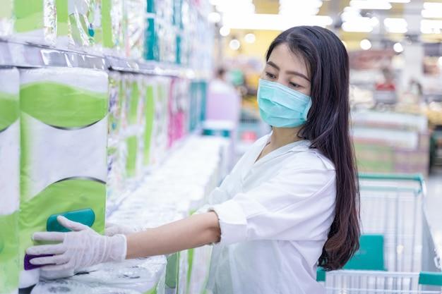 Neue normale asiatische frau, die gesichtsmaskeneinkauf im supermarktkaufhaus trägt
