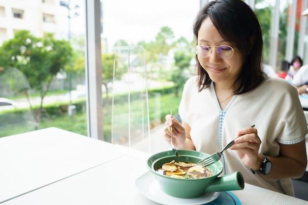 Neue normale asiatische frau mittleren alters essen mit einer plastikplatte, um die ausbreitung zu verhindern