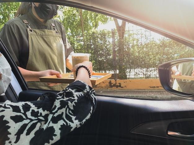 Neue normale frau, die in einem auto sitzt und eiskaffee von der durchfahrt bekommt