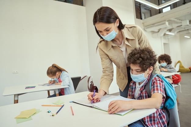 Neue normale moderne lehrerin, die eine schützende gesichtsmaske trägt und kleinen jungen in klassenzimmerkindern hilft