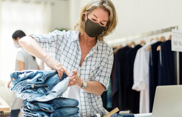 Neue normalität im einzelhandel, geschäftsinhaber trägt eine maske
