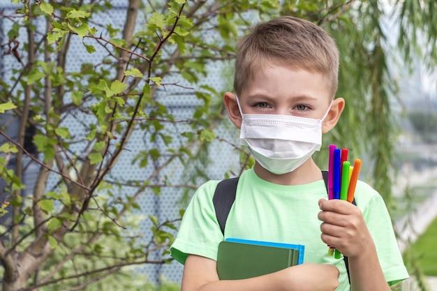 Neue normalität, zurück in die schule. schüler trägt medizinische maske und rucksack mit lehrbuch und filzstiften im freien