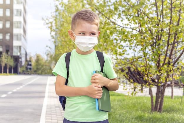 Neue normalität, zurück in die schule. schuljunge, der medizinische maske und rucksack trägt, die lehrbuch draußen halten