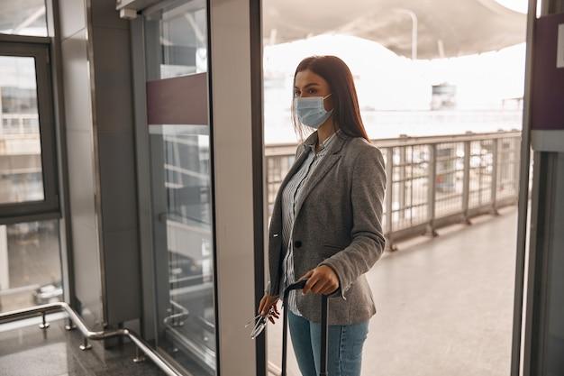 Neue ordnung an flughäfen. frau mit maske im terminal mit gepäck allein in der nähe von panoramafenstern