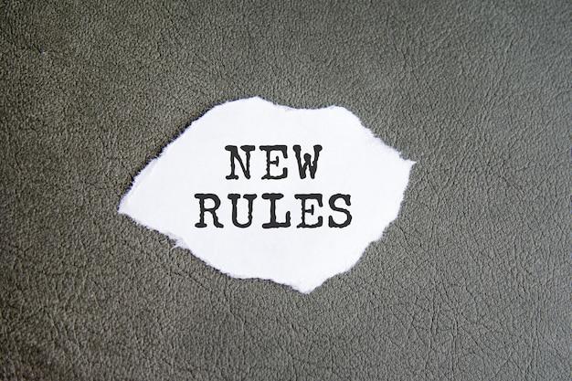 Neue regeln-zeichen auf dem zerrissenen papier auf grauem hintergrund, geschäftskonzept