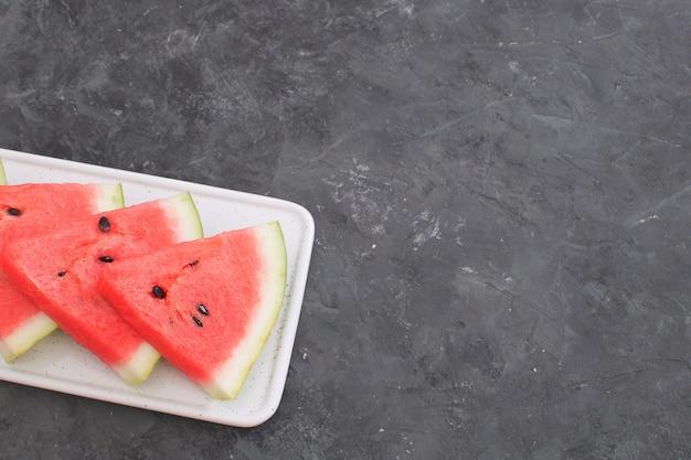 Neue rote wassermelone schneidet schwarzen hintergrund