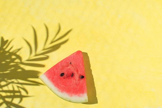Neue rote wassermelonenscheibe auf draufsicht des gelben hintergrundes