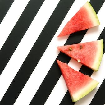 Neue rote wassermelonenscheibe auf gestreiftem hintergrund