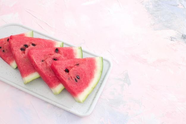 Neue rote wassermelonenscheiben lokalisierter pastellrosahintergrund