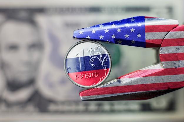 Neue sanktionen gegen die russische wirtschaft. zangen mit usa-flagge drückten den rubel mit russischer flagge zusammen.