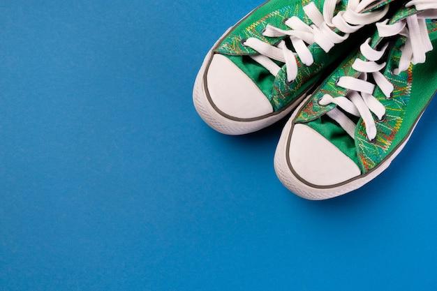 Neue saubere grüne athletische turnschuhe mit schnürsenkeln auf einem hellblauen hintergrund.