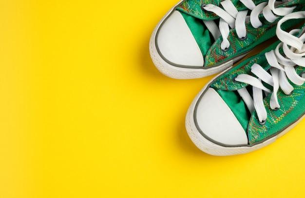 Neue saubere grüne athletische turnschuhe mit schnürsenkeln auf einem leuchtend gelben hintergrund.