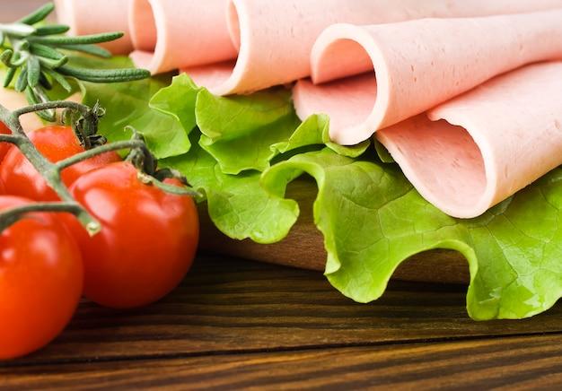 Neue schinkenscheiben mit salat- und kirschtomate auf dem hölzernen brett
