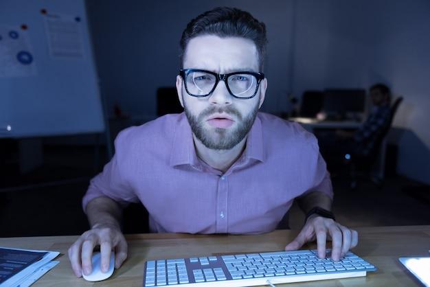 Neue software. ernsthafter, hart arbeitender professioneller programmierer, der sich nach vorne beugt und auf den computerbildschirm schaut, während er an der neuen software arbeitet