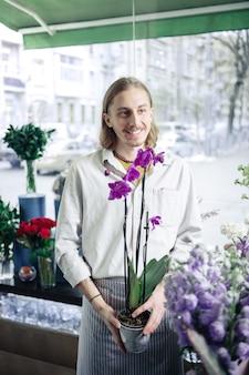 Neue sorte. fröhlicher florist, der ein lächeln auf seinem gesicht behält und zur seite schaut