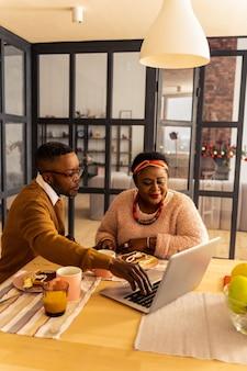 Neue technologie. angenehmes afroamerikanisches paar, das zusammen am tisch sitzt, während sie ihren laptop zusammen benutzen