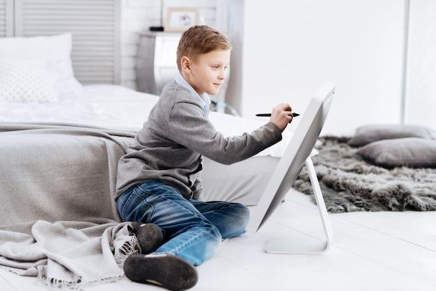 Neue technologie. erfreuter kreativer netter junge, der auf dem boden sitzt und einen stift verwendet, während er auf dem digitalen bildschirm zeichnet