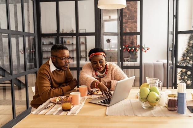 Neue technologien. positive gut aussehende frau, die den knopf auf ihrem laptop drückt, während sie zusammen mit ihrem ehemann davor sitzt